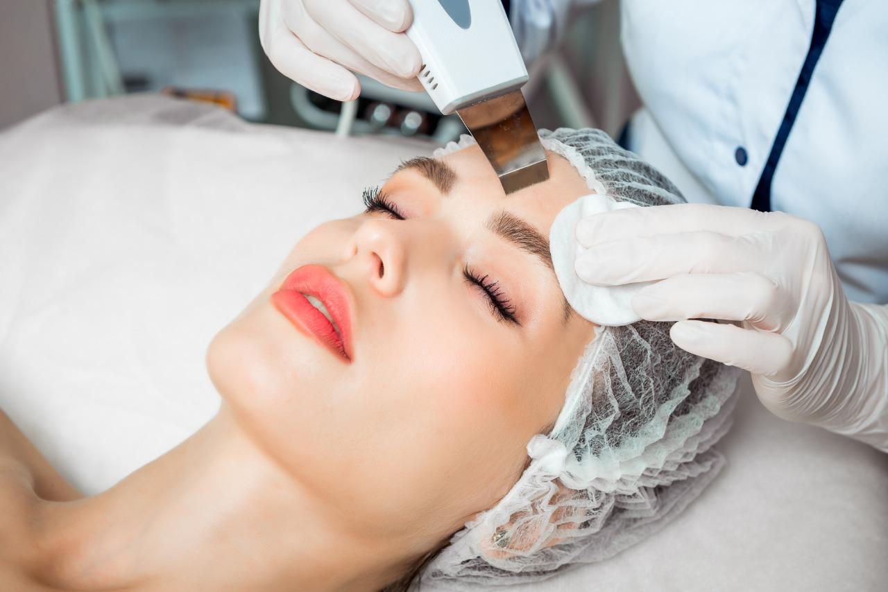 Mulher fazendo procedimento estetico em outra mulher